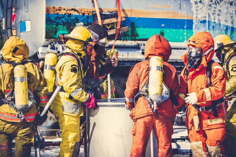 I vigili del fuoco in uniforme del pompiere stanno controllando il loro afte dell'attrezzatura fotografie stock libere da diritti