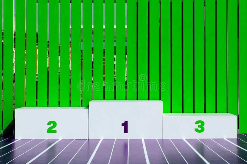 I vincitori mettono a disposizione una chiusura bianca su sfondo verde Vittoria, Premio Pedestal Primo, secondo, terzo posto fotografia stock