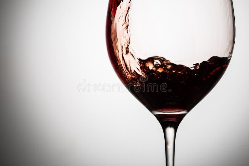 I vini rossi ondeggiano i flussi giù la parete del bicchiere di vino fotografia stock libera da diritti