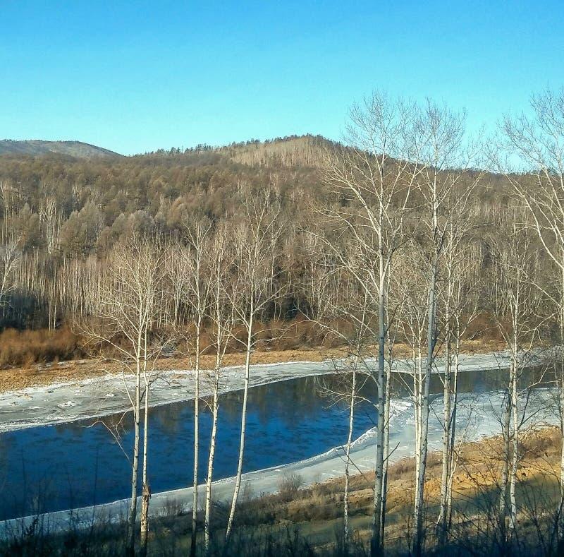 I vinter flödar floden bland kullarna och de djupfrysta bankerna royaltyfria foton