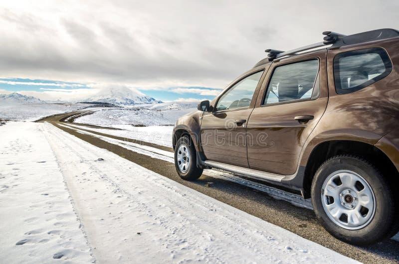 I vintern som är dold med snö SUV som kör på en väg som lämnar i himmel royaltyfri fotografi