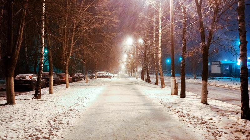 I vintern i stad en nattgata med phonories, en stark vind av snö I parkera täckas vägen med snö arkivbild