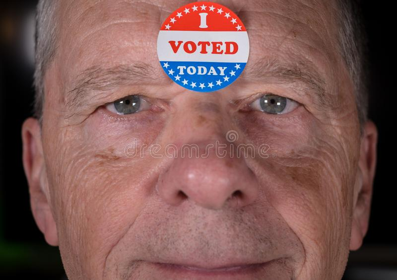 I Voted Today paper sticker on mans forehead with warm smile at camera. I Voted Today sticker on senior caucasian mans forehead with warm smiling look at camera stock photography