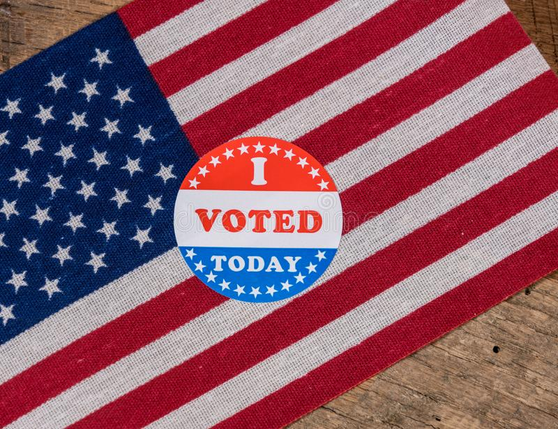 I Voted Today paper sticker on US Flag and rural wooden table. I Voted Today sticker for voters in the US elections with USA flag on rustic wooden table royalty free stock image
