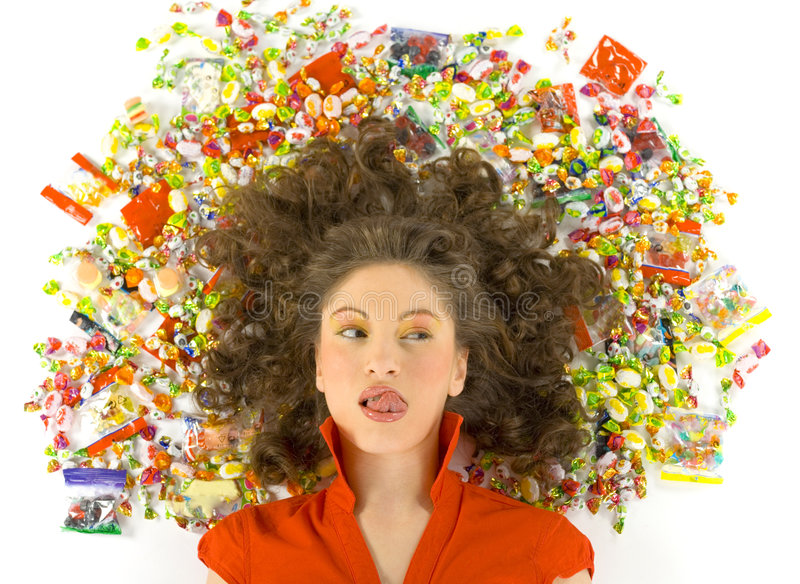 I want candy. Young, beautiful woman lying on floor among candys. Looking at candys and licking her lips. Front view, white background stock images