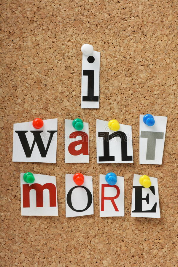 I Want More. The phrase I Want More in cut out magazine letters pinned to a cork notice board stock photo