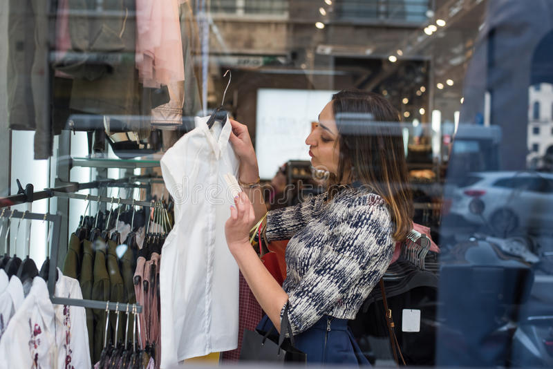 I want a new shirt. Brunette girl with long dark hair looking holding a of female white shirt in a store and smiling stock images