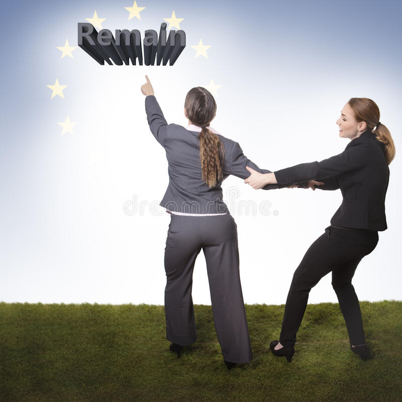 I want to remain. Two business women one want to remain and the other is pulling her wanting her to stay stock photo