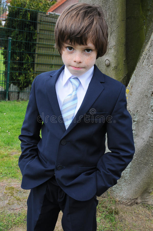 I want to take off my suit. Cute little boy doesnt want to be dressed like a businessman stock photo