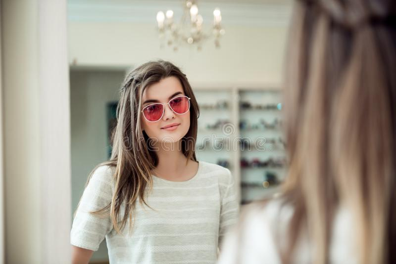 I will be most stylish woman on beach. Portrait of attractive caucasian young brunette standing in optician store royalty free stock photo