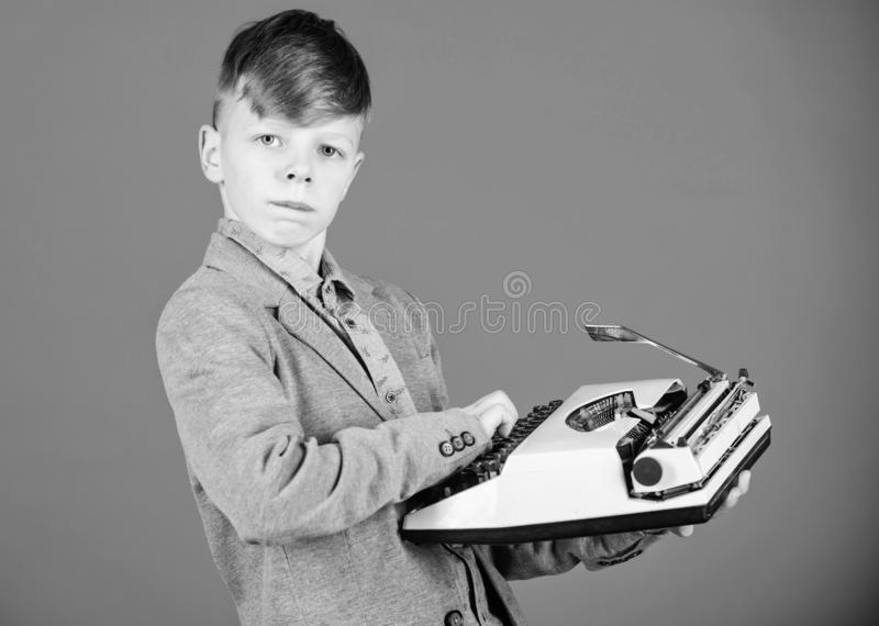 I will be a news reporter. A cute child reporter on blue background. Small reporter holding retro typewriter. Little. Reporter typewriting message or article on stock photo