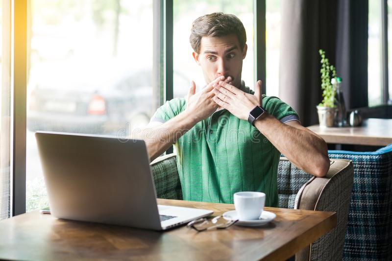 I will be quiet! Young shocked businessman in green t-shirt sitting, looking at laptop screen with unbelievable face and covering royalty free stock images