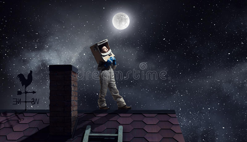 I will become astronaut and fly to space . Mixed media. Funny girl in space costume on house roof dreaming she is astronaut stock photo