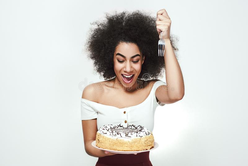 I will eat it right now! Excited cute afro american woman with curly hair is holding a fork in one hand and birthday royalty free stock photo