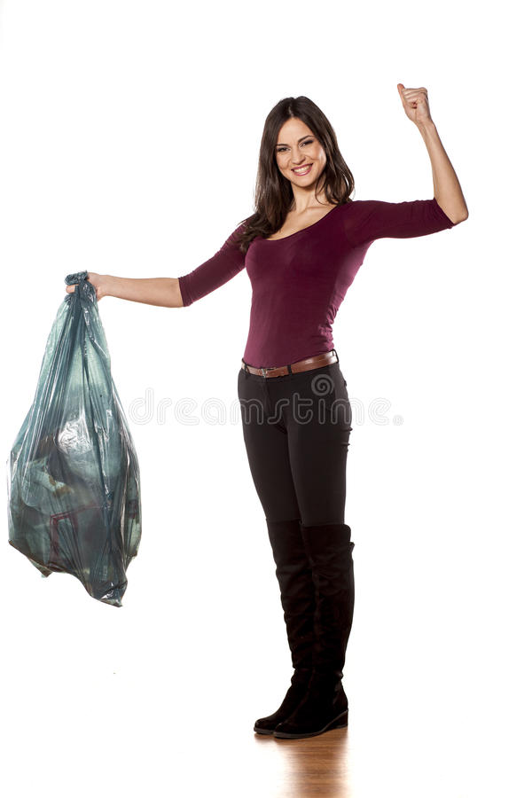 I win. Happy woman holding garbage bag and showing winning gesture on white background royalty free stock photos