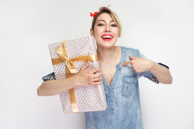 I am winner! Confident beautiful young woman in casual blue denim shirt and red headband standing, holding present and pointing stock photography