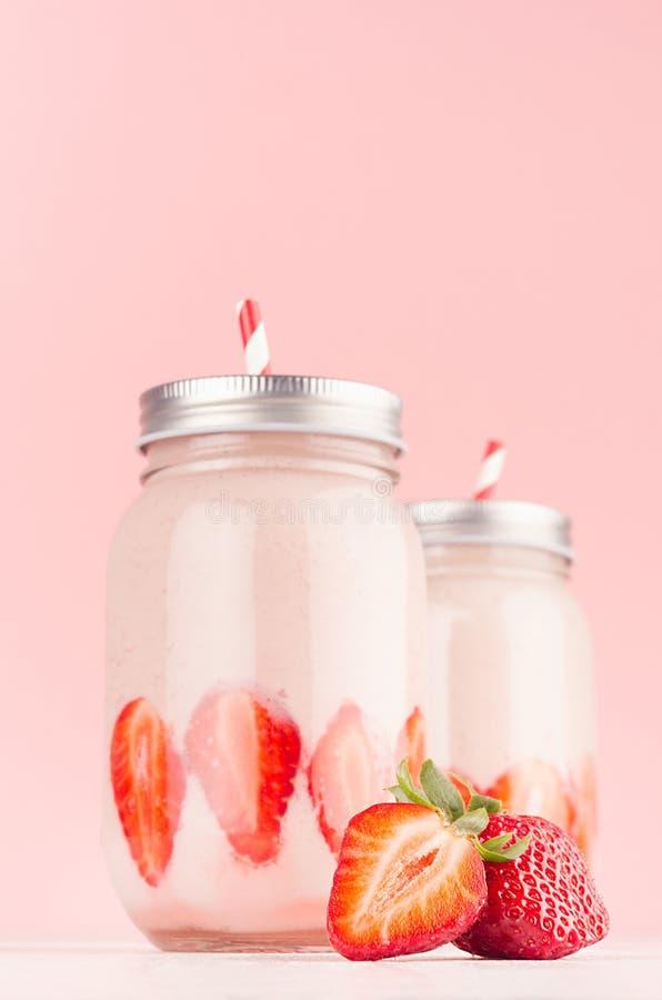 I yogurt delicati della fragola in due barattoli decorati hanno affettato le bacche mature con i coperchi d'argento e le paglie a immagine stock