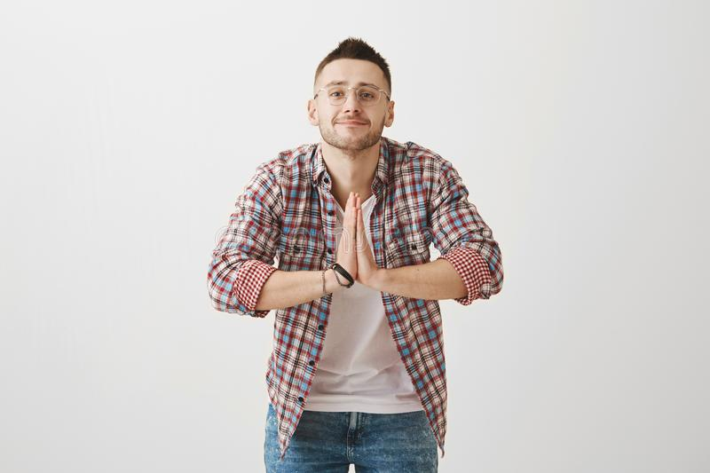 I am at your service, sensei. Indoor shot of positive emotive young guy in glasses bowing while greeting someone in stock images