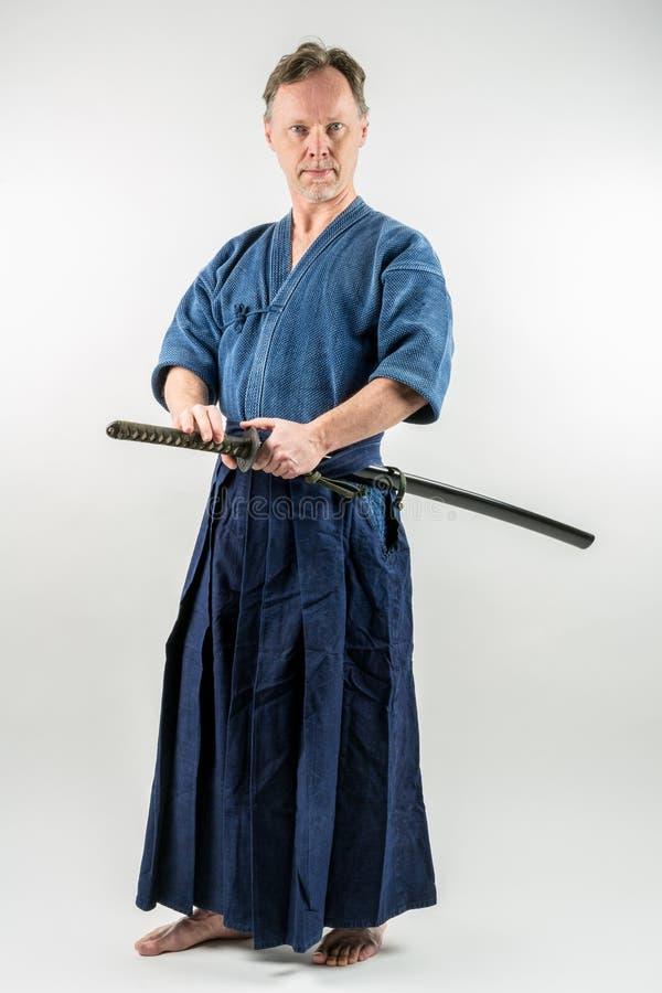Iaido di formazione maschio caucasico adulto circa per estrarre una spada giapponese con lo sguardo messo a fuoco fotografia stock