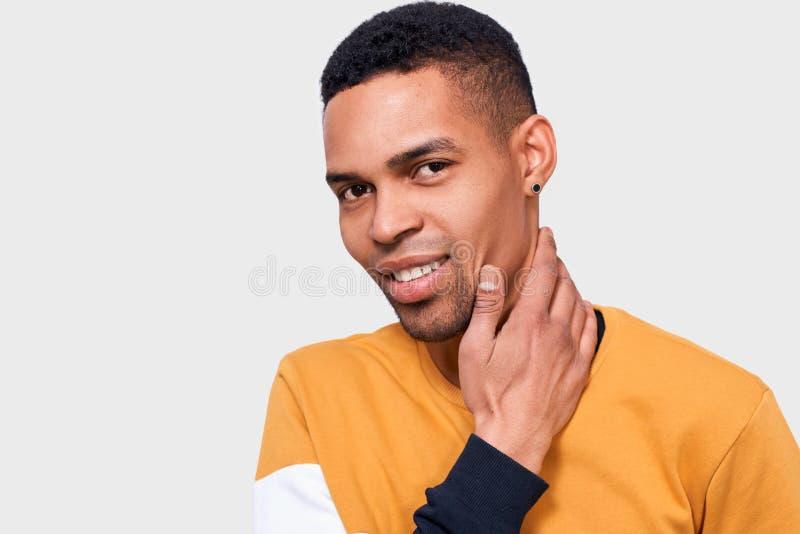Iamge do homem afro-americano considerável novo que toca em seus cara e pescoço com mão e que olha à câmera na parede branca do e fotos de stock royalty free