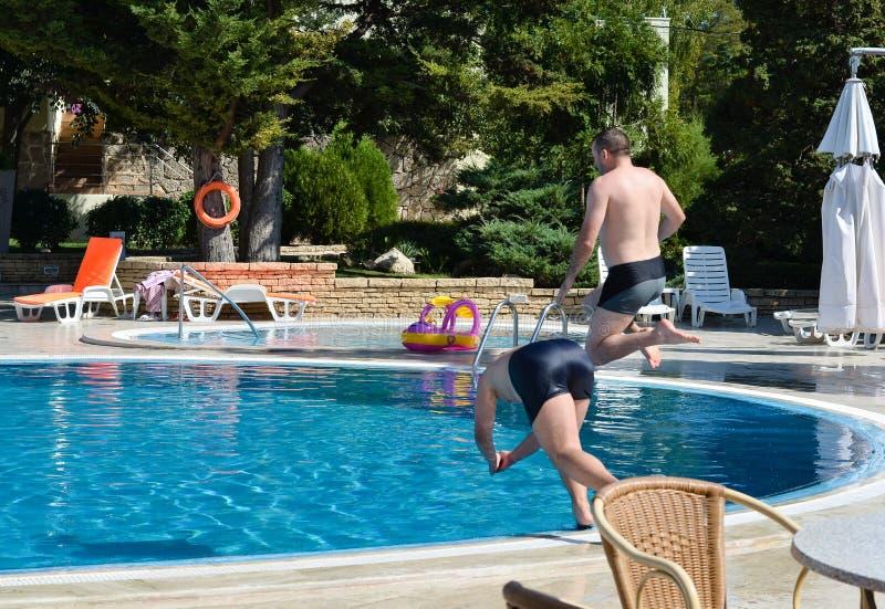 Iasi, Roumanie - 28 juillet 2019 - deux jeunes hommes sautant dans la piscine photographie stock