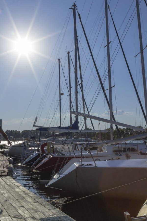 Iate amarrados ao cais dusk Sol de ajuste com raios longos no céu foto de stock royalty free