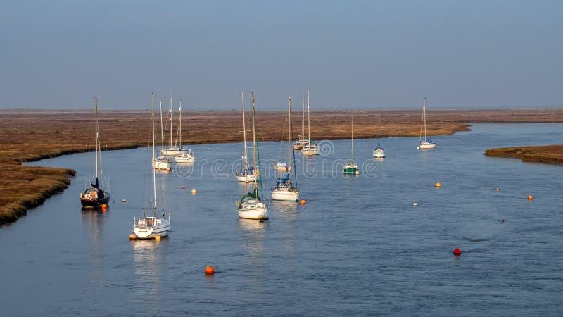 Iate amarrados como os grupos do sol no estuário do leste da frota, Norfolk foto de stock