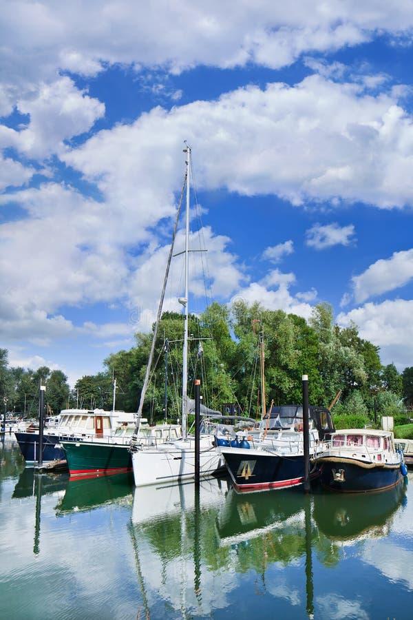 Iate amarrados em um porto verde, Woudrichem, os Países Baixos imagem de stock royalty free