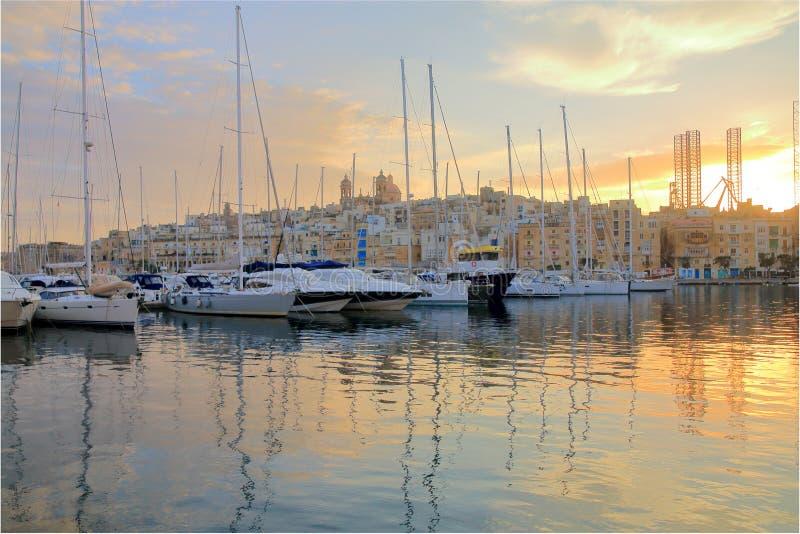Iate amarrados no porto de Malta nos raios do sol de ajuste foto de stock