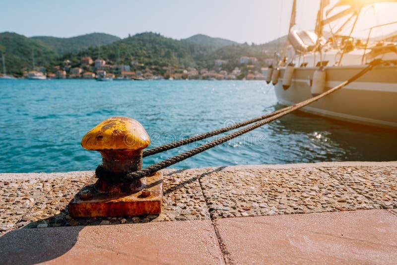 Iate bonito amarrado no cais Raios de sol do sentimento do verão, luz solar da manhã Férias nas ilhas gregas fotos de stock royalty free