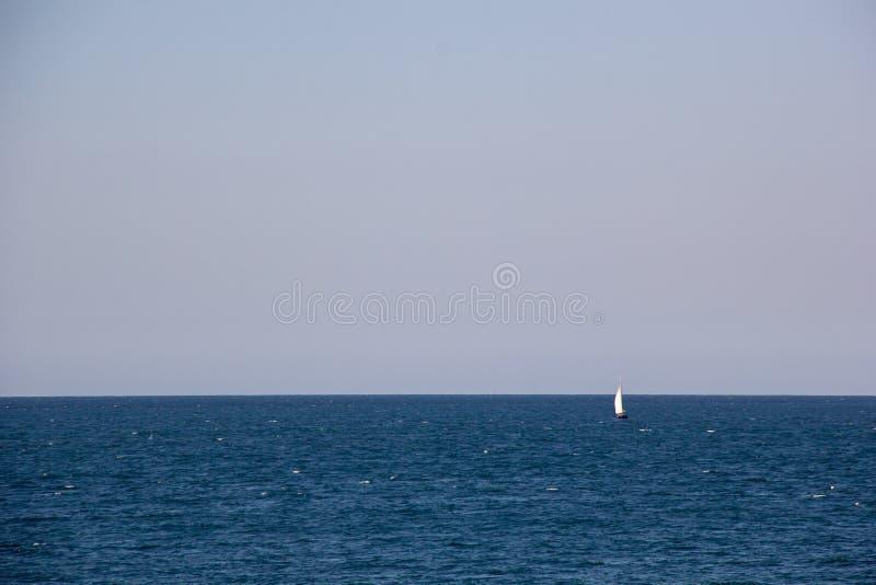 Iate de navigação pequeno com as velas brancas grandes no mar aberto no horizonte foto de stock