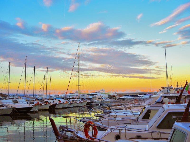 Iate e veleiros luxuosos no porto no por do sol Estacionamento marinho de barcos de motor modernos em Liguria, Italia imagens de stock royalty free