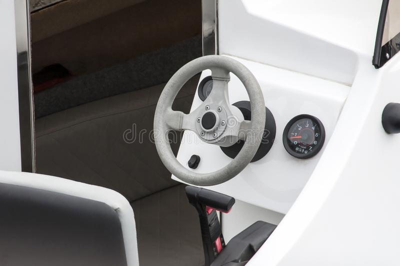 Iate, interior do barco a motor, volante e close up novos limpos brancos da cabina do piloto da cadeira dos capitães fotos de stock