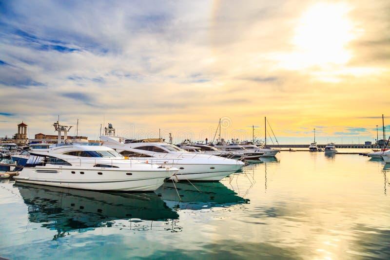 Iate luxuosos no por do sol Doca marinha do motor e de barcos de navigação modernos na luz do sol, mar da água azul, arco-íris co imagens de stock royalty free