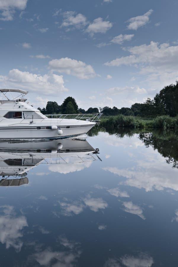 Iate majestoso em um rio em um dia de verão ensolarado com reflexões fotos de stock