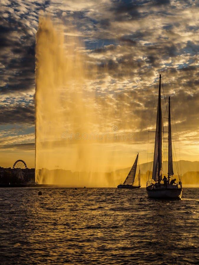 Iate que navegam no porto de Genebra, Suíça no por do sol imagem de stock