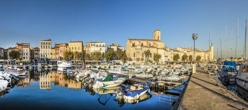 Iate que refletem na água azul no porto velho da cidade do La Ciota foto de stock