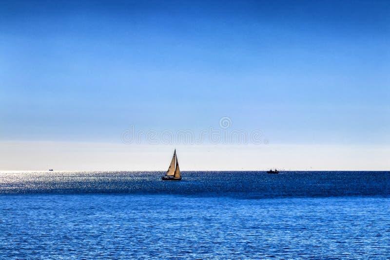 Iate solitário para fora em um mar azul profundo fotografia de stock