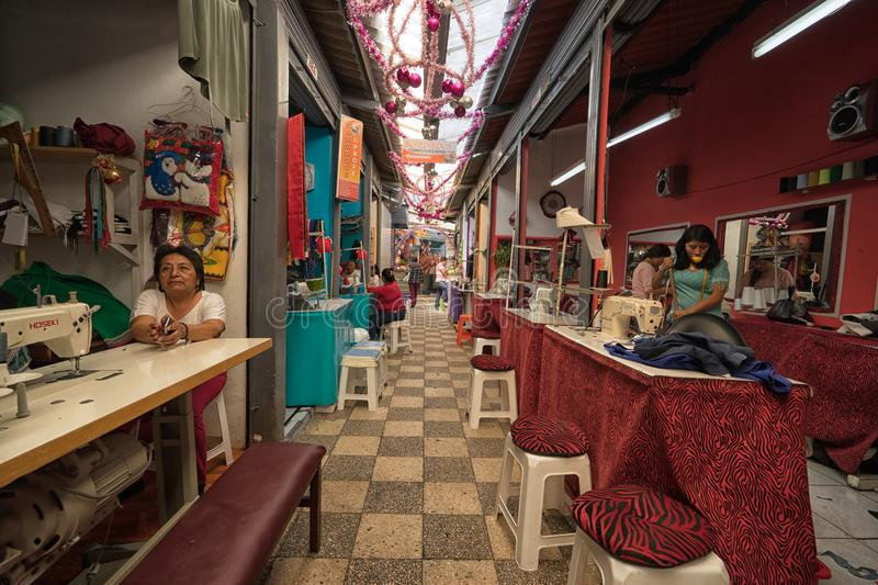 Alteration shops in Ibarra, Ecuador. Ibarra, Ecuador - January 5, 2018: women workers in the alteration shop section of the local market stock image