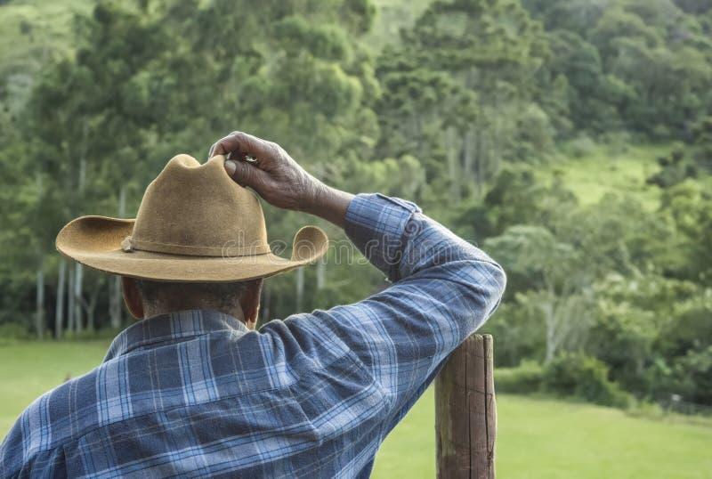 Ibitipoca, Lima Duarte, Minas Gerais, Brasil - 13 de março de 2016: Garoto com chapéu tradicional inclinado sobre vara de vedação imagem de stock