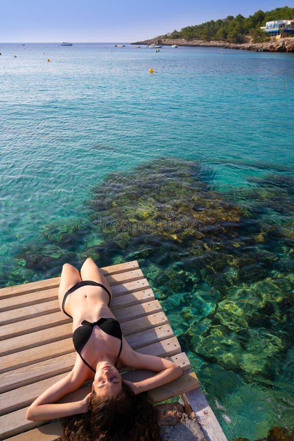 Ibiza bikiniflicka som kopplas av på den Portinatx stranden fotografering för bildbyråer