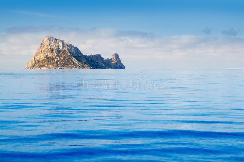 Ibiza Es Vedra island in calm blue water stock photos