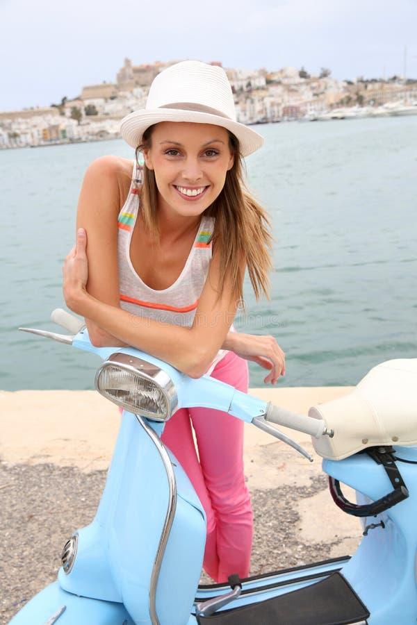 Ibiza que visita sonriente de la muchacha con la vespa fotos de archivo libres de regalías