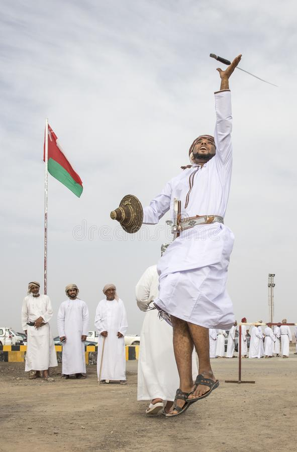 Omani man throwing a sword in a air to demonstrate his skill royalty free stock image