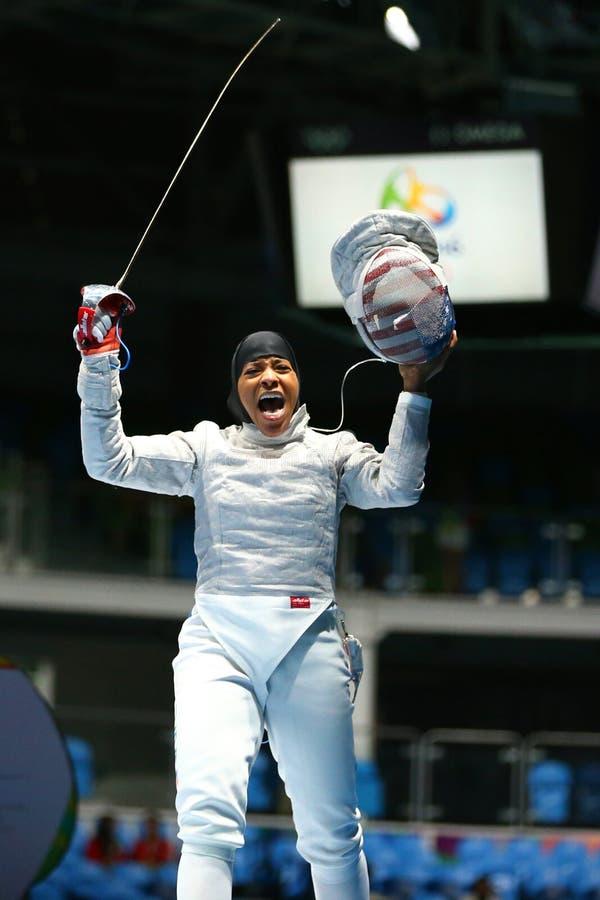 Ibtihaj Мухаммед Соединенных Штатов празднует победу в сабле ` s женщин индивидуальной Рио 2016 Олимпийских Игр стоковое фото
