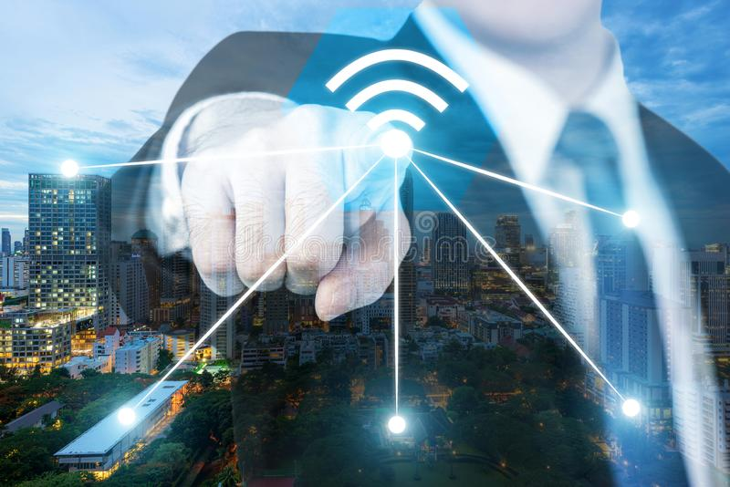 Ic?ne de wifi de pouss?e d'homme d'affaires sur la ville et le concept de connexion r?seau Ville futée de Bangkok et réseau de tr images stock