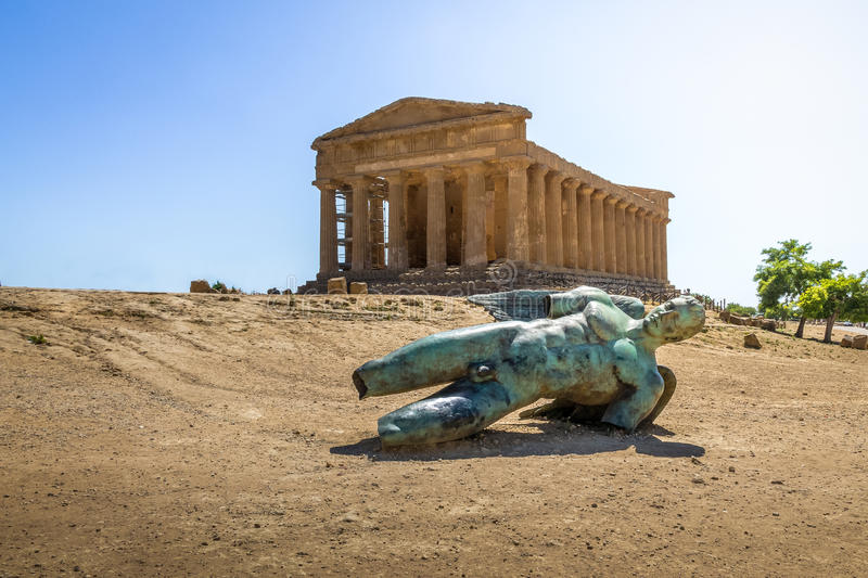 Icarus bronze statue and Temple of Concordia in the Valley of Temples - Agrigento, Sicily, Italy royalty free stock photos