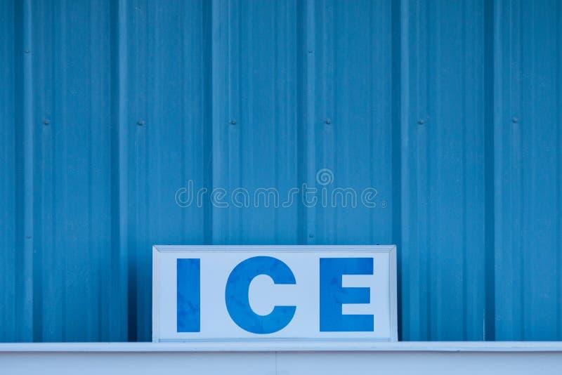 ICE λέξης στα κεφαλαία γράμματα στο σημάδι μπροστά από το κρύο μπλε μέταλλο στοκ φωτογραφία με δικαίωμα ελεύθερης χρήσης