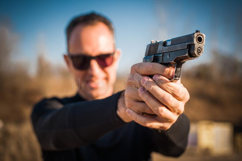 Police agent and bodyguard pointing pistol to protect from attacker royalty free stock images