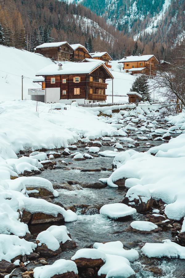 Free Ice And Snow Covered Creek On A Cold Winter Day Infront Of Traditional Wooden Cabins Of Little Mountain Village Royalty Free Stock Photo - 167999005